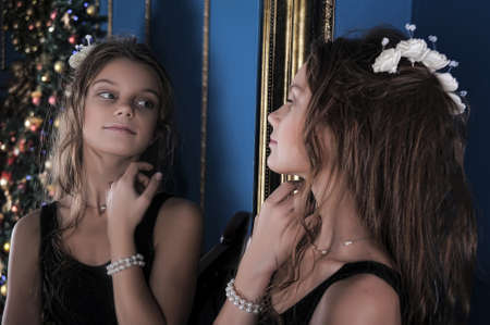 Girl looks in the mirror. photo