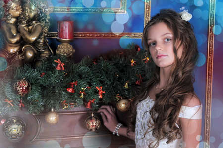 Girl in white dress in the fireplace on background glowing Christmas tree.