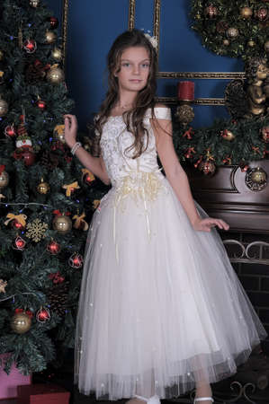 hearthside: Girl in white dress in the fireplace on background glowing Christmas tree.