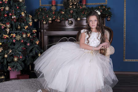 Girl in white dress in the fireplace on background glowing Christmas tree. photo