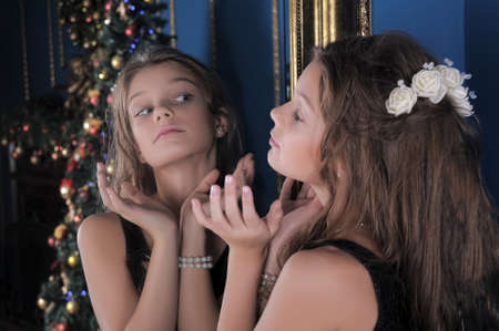 Girl admires herself in the mirror photo