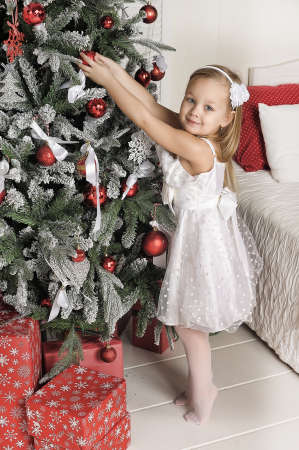 teddy wreath: Girl in white dress at the Christmas tree on Christmas.