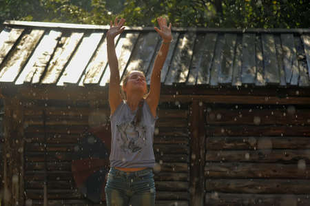 Happy teen girl in T-shirt and shorts in the summer rain. photo