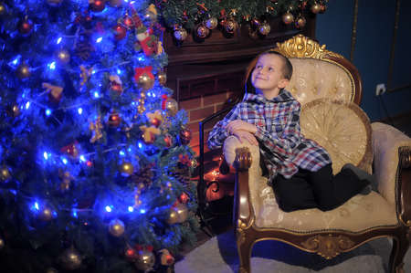 boy near glowing Christmas tree photo