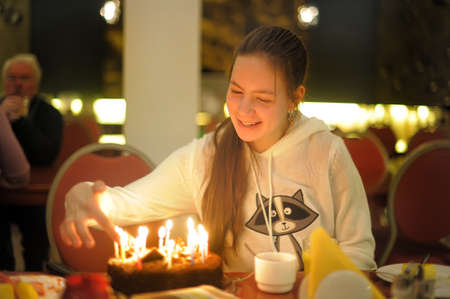 Happy teen girl and cake with candles photo