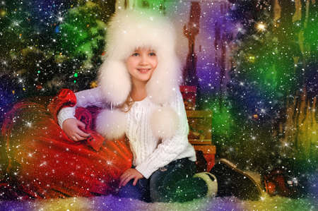 topknot: Girl in a white fur hat with a bag of gifts on Christmas. Stock Photo