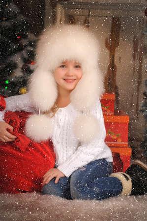 esquimales: Chica en un sombrero de piel blanca con una bolsa de regalos en Navidad. Foto de archivo