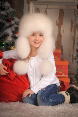 esquimales: Girl in a white fur hat with a bag of gifts on Christmas. Foto de archivo