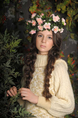 Young beautiful girl with a wreath of flowers on her head photo
