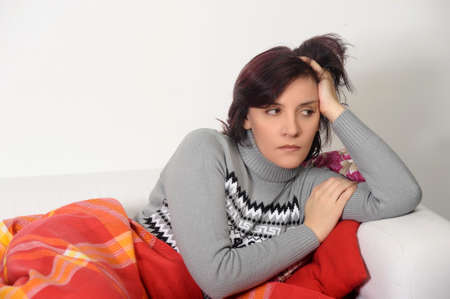 couching: Woman in depression sitting on the couch nestled rug.