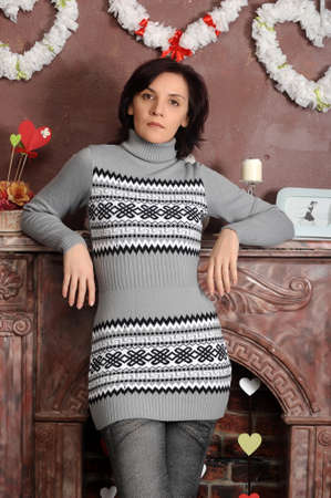 dolor: Sad young woman in a gray sweater dress at fireplace. Stock Photo