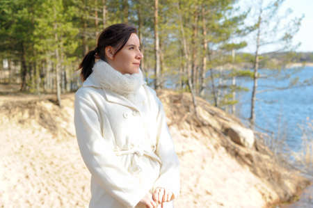 mackintosh: Young woman in a white coat in the spring in nature.