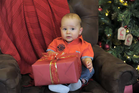 kid with a gift at the Christmas tree photo
