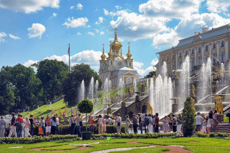 Tourists visit the sights of the lower park of Peterhof.