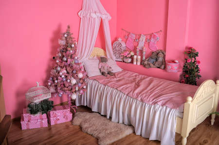 Interior of childrens room in pink tones with Christmas tree. photo