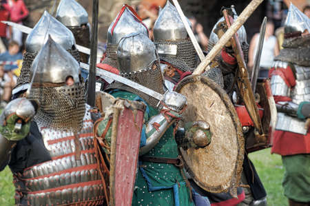 crusaders: Fight between the pedestrian knights in a heavy armor in a medieval castle against a stone wall.