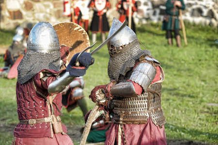 showmanship: Fight between the pedestrian knights in a heavy armor in a medieval castle against a stone wall.