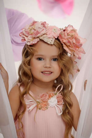 Portrait of a charming little girl with a wreath of roses. photo