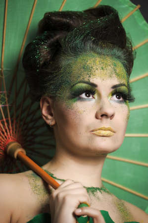 edwardian: Girl in green with creative make-up with the Chinese umbrella.