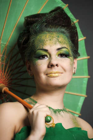 Girl in green with creative make-up with the Chinese umbrella. photo