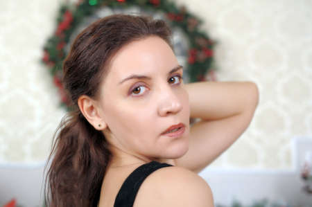 Beautiful brunette in a room with Christmas decorations. photo