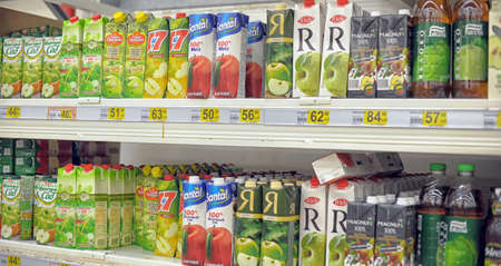 abundant: Supermarket Shelves Full With Different Natural Fruit Juice Bottles And Cartons. Editorial