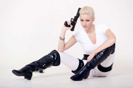 cartridge belt: Sexy blonde with a gun in hand. Stock Photo