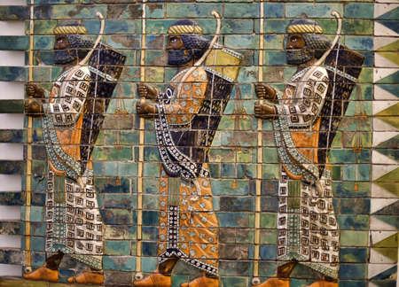 ishtar gate of babylon: Babylonian Archers. These men with bows and spears are depicted at the Ishtar Gate, one of the gates to ancient Babylon. The base relief was reconstructed at the Pergamon Museum, in Berlin, Germany. Stock Photo