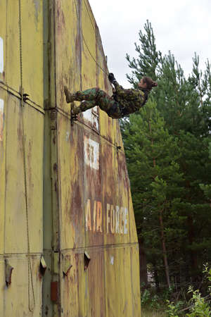 Girl hangs from a building on the climbing equipment, Summer training camp for teen, Russia. photo