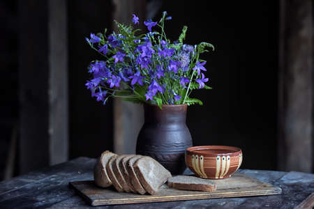A rustic still life with a bunch of bluebells in a ceramic vase and a bowl of sliced bread on a board. Stock Photo