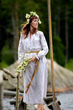 slavs: Woman in ethnic clothes with a wreath of flowers by the water on Midsummer.