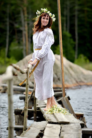 midsummer: Woman in ethnic clothes with a wreath of flowers by the water on Midsummer.