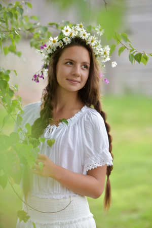 plaits: Beautiful young girl with plaits and daisies birch. Stock Photo