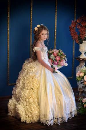 Giovane principessa in un elegante abito bianco con fiori tra i capelli.
