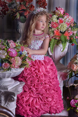 young princess in a smart dress next to flowers Stok Fotoğraf