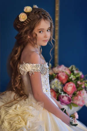 Young princess in an elegant white dress with flowers in her hair