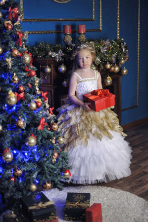 curtsy: Young beautiful princess in white gold smart dress at the Christmas tree at Christmas.