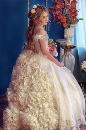 chandelier  kids: Young princess in an elegant white dress with flowers in her hair.