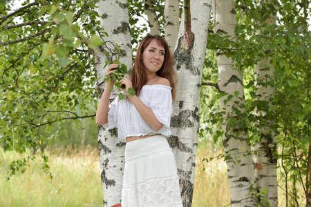 european white birch: Brunette in a white blouse and skirt near the birch.