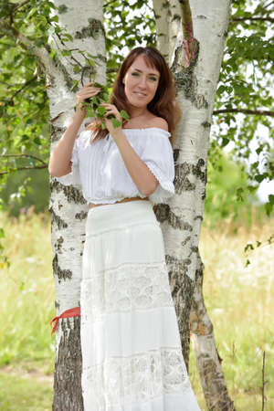 european white birch: Brunette in a white blouse and skirt near the birch.