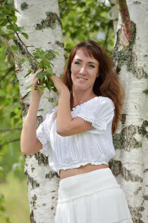 Brunette in a white blouse and skirt near the birch.