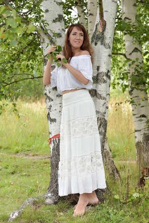 european white birch: Brunette in a white blouse and skirt near the birch