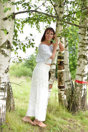 european white birch: Brunette in a white blouse and skirt near the birch