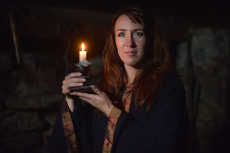 Portrait of a woman in the dark with a candle