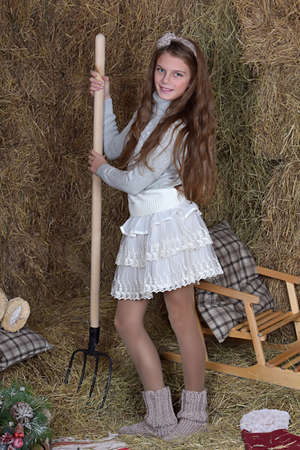 barn girls: Girl with a pitchfork in his hand against the background of haystacks. Stock Photo