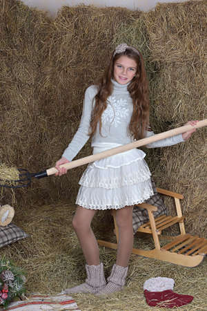 Girl with a pitchfork in his hand against the background of haystacks. Stock Photo