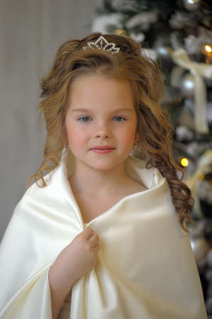 young tree: Winter princess in white dress at the Christmas tree. Stock Photo
