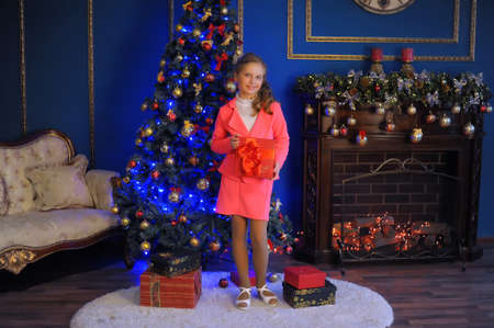 catchy: Girl in a pink suit in Christmas the near Christmas tree.