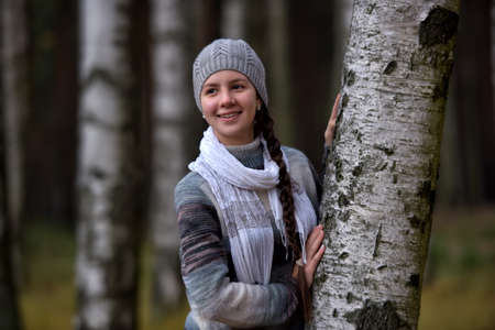 grey eyed: Girl in a gray beret and sweater near the birch. Stock Photo