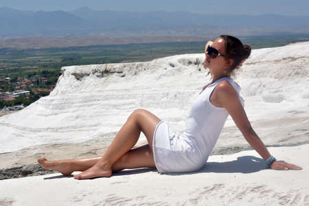 Teen girl in white on a background of calcium Pamukkale travertine.